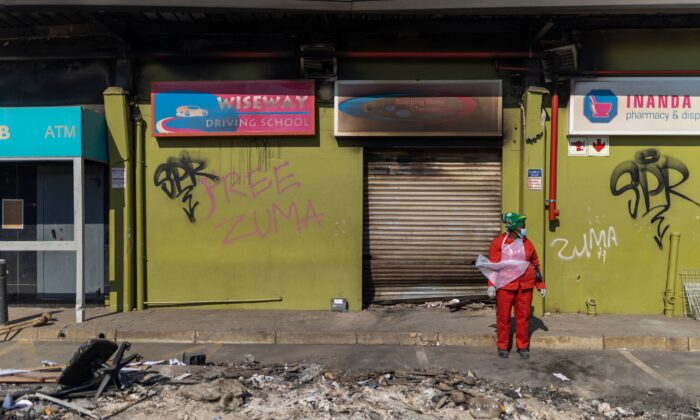 """Following several days of looting and unrest, a woman can be seen during a cleaning operation of the Dube Village Mall in Durban next to """"Free Zuma"""" graffiti on July 17, 2021. (Guillem Sartorio/AFP via Getty Images)"""