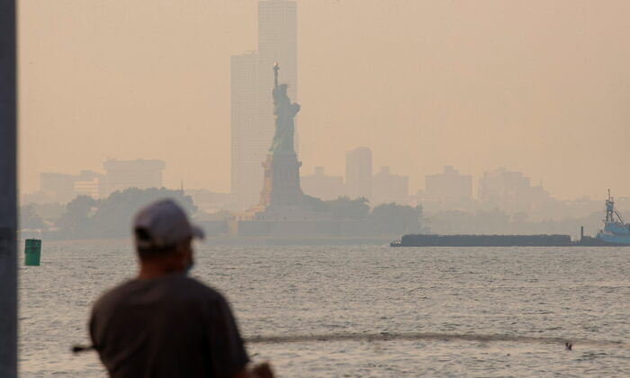 The Statue of Liberty is seen through a cover of wildfire smoke in New York Harbor as seen from Brooklyn, N.Y., on July 21, 2021. (Brendan McDermid/Reuters)