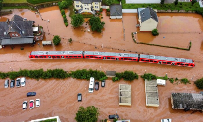 A regional train sits in the flood waters at the local station after it was flooded by the high waters of the Kyll river in Kordel, Germany, on Thursday July 15, 2021. (Sebastian Schmitt/dpa via AP)