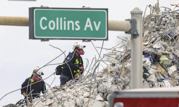 Search and rescue team members climb the debris field of the 12-story oceanfront condo, Champlain Towers South along Collins Avenue in Surfside, Fla., on July 7, 2021. (Al Diaz/Miami Herald via AP)
