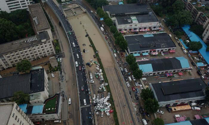 An aerial view shows cars sitting in floodwaters at the entrance of Jingguang Expressway tunnel after heavy rains hit the city of Zhengzhou in China's central Henan province on July 22, 2021. (Noel Celis / AFP)