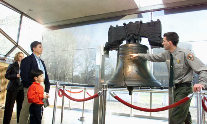 A National Park Service ranger points out the larger of two cracks in the Liberty Bell to a family in Philadelphia, on Feb. 21, 2002.  (Don Murray/Getty Images)