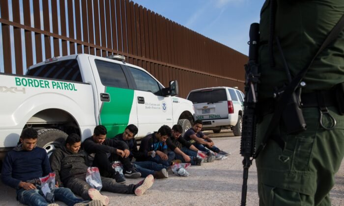 After being apprehended by Border Patrol, illegal immigrants wait to be transported to a central processing center shortly after they crossed the border from Mexico into the United States in the Rio Grande Valley Sector near McAllen, Texas March 26, 2018. (Loren Elliott/AFP via Getty Images)