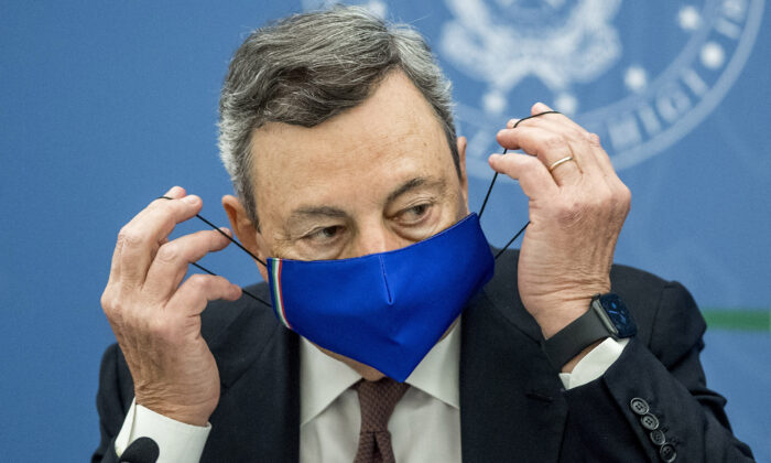 Italian Prime Minister Mario Draghi removes his face mask during a press conference in Rome on July 22, 2021. (Roberto Monaldo/Pool/AFP via Getty Images)