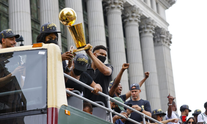 Milwaukee Bucks' Giannis Antetokounmpo holds up the NBA Championship trophy during a parade and celebration for the basketball team in Milwaukee, Wis., on July 22, 2021. (Jeffrey Phelps/AP Photo)