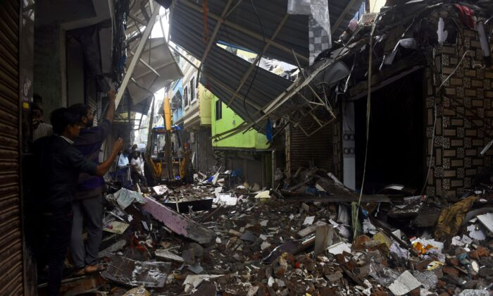 People use their mobile phones to take pictures of a collapsed building following rains in Mumbai, India, on July 23, 2021. (Stringer/Reuters)