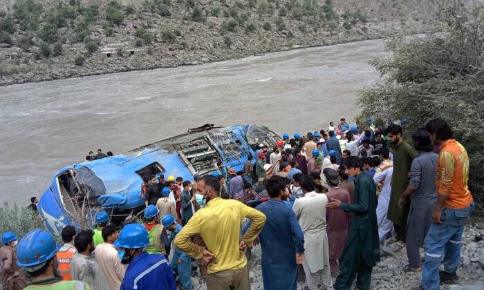 Rescue workers and onlookers gather around a wreck after a bus plunged into a ravine following a bomb explosion, which killed 12 people including 9 Chinese workers, in Kohistan district of Khyber Pakhtunkhwa province on July 14, 2021. (Stringer/AFP via Getty Images)
