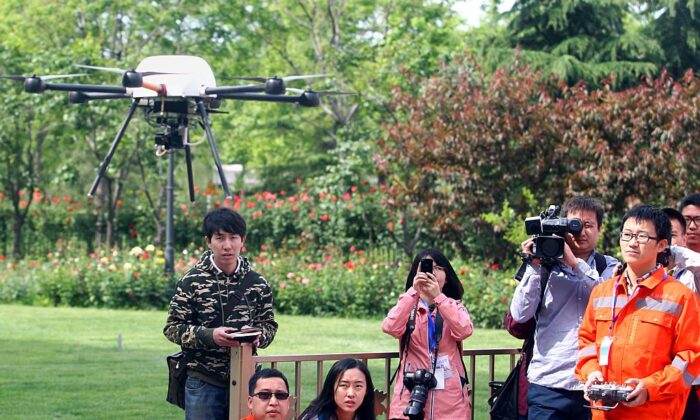This picture, taken on May 12, 2015, shows people watching a demonstration of an unmanned drone during a campaign for disaster prevention and reduction in Beijing.  China forbids any flights, manned or unmanned, without prior approval from the air force, civil aviation authorities, and the local air traffic control bureau. (STR/AFP via Getty Images)