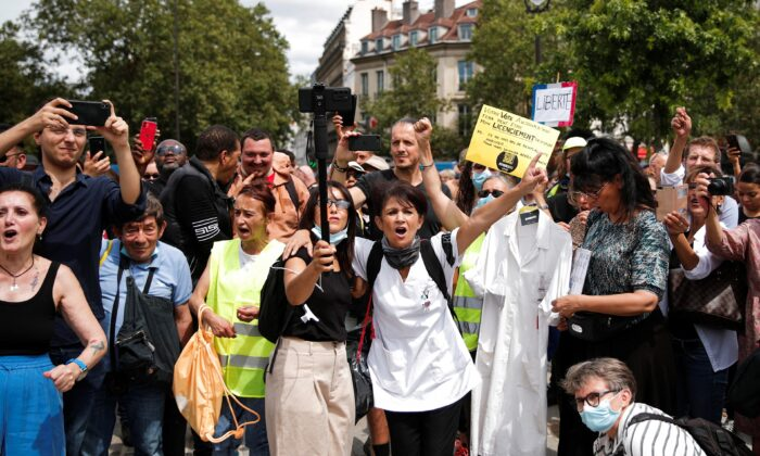 Protesters hold placards and banners during a demonstration against France's COVID-19 restrictions in Paris, on July 24, 2021. (Benoit Tessier /Reuters)