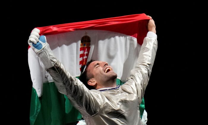 Aron Szilagyi of Hungary celebrates winning the gold medal after defeating Luigi Samele of Italy compete in the men's individual final Sabre competition at the 2020 Summer Olympics, in Chiba, Japan, on July 24, 2021. (AP Photo/Hassan Ammar)