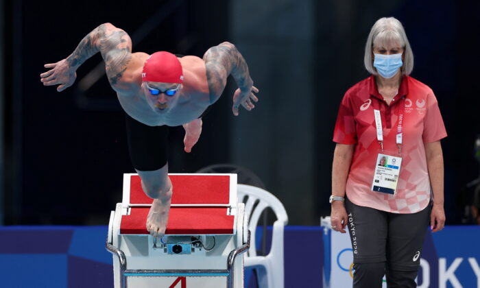 Adam Peaty of Britain in action as a referee wearing a mask looks on at Tokyo 2020 Olympics in Tokyo, Japan, on July 24, 2021. (Kai Pfaffenbach/ Reuters)