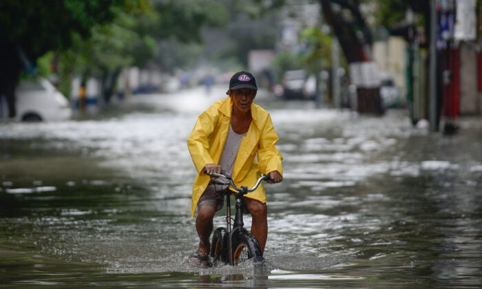 A man on a bicycle wades through a flooded street in Manila, Philippines, on July 24, 2021. (Lisa Marie David/Reuters)