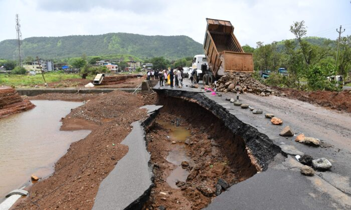 People gather along a road partially washed away at Mahad, India, on July 24, 2021. (Indranil Mukherjee/AFP via Getty Images)