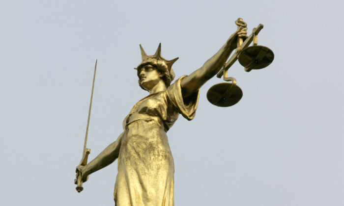 A statue representing the scales of justice is seen on the roof of the Old Bailey courts in central London, on Jan. 26, 2007. (Toby Melville/Reuters)