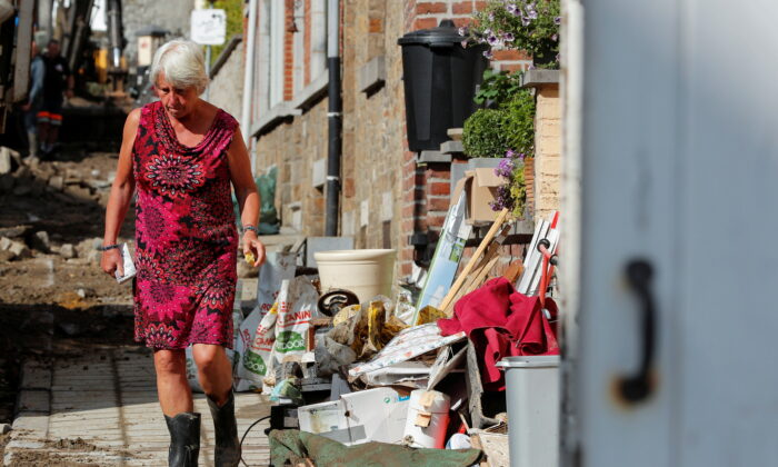 A woman walks in an area affected by heavy rainfall in Dinant, Belgium, on July 25, 2021. (Johanna Geron/Reuters)