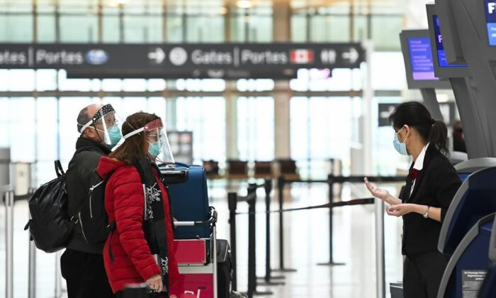 People check in at the international departures at Pearson International Airport on Dec. 14, 2020. (The Canadian Press/Nathan Denette)