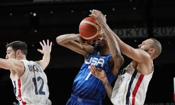 United States' forward Kevin Durant (7) and France's Evan Fournier fight for control of the ball during a men's basketball preliminary round game at the 2020 Summer Olympics in Saitama, Japan, on July 25, 2021. (AP Photo/Eric Gay)