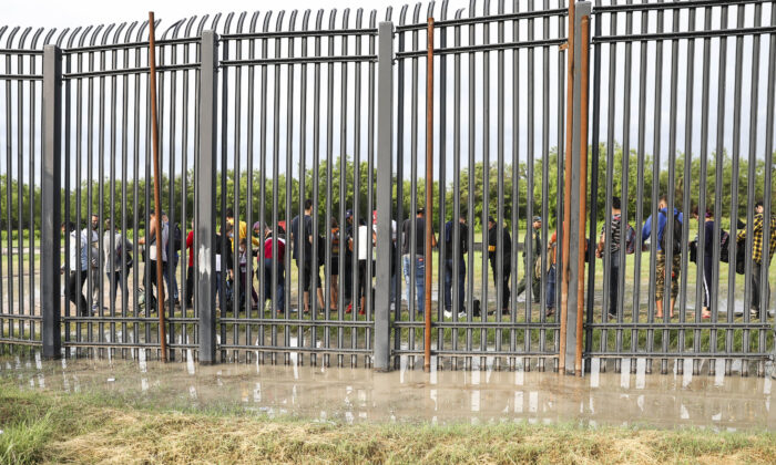 Illegal immigrants wait to be picked up by Border Patrol after crossing the Rio Grande from Mexico into Del Rio, Texas, on July 20, 2021. (Charlotte Cuthbertson/The Epoch Times)