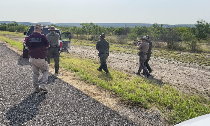 Texas, Nebraska, and Iowa State Troopers, along with Border Patrol and the Kinney County Constable, prepare to search a stolen vehicle in Kinney County, Texas, on July 21, 2021. (Charlotte Cuthbertson/The Epoch Times)