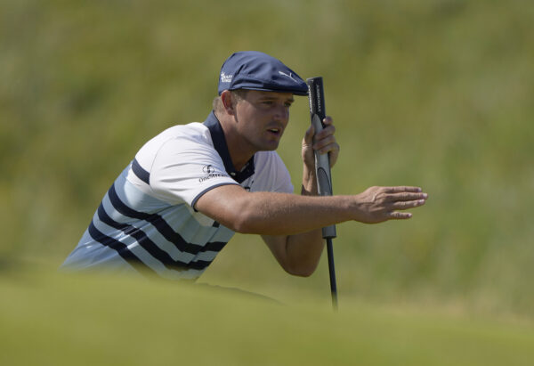 Bryson DeChambeau gestures as he lines up his putt