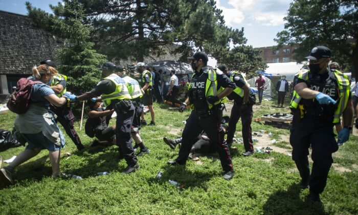 Police remove encampment supporters as they clear the Lamport Stadium Park homeless camp in Toronto on July 21, 2021. (The Canadian Press/Chris Young)