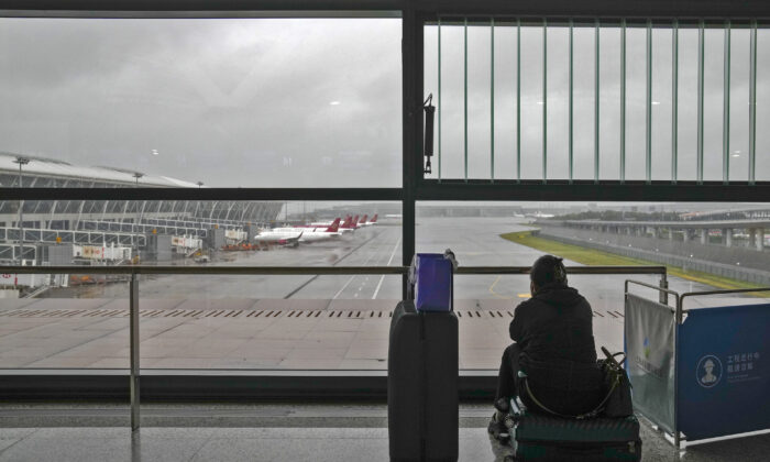 A passenger sits on her luggage watching the passenger airplanes parked on the tarmac after all flights were canceled at Pudong International Airport in Shanghai, China, on July 25, 2021. (Andy Wong/AP Photo)