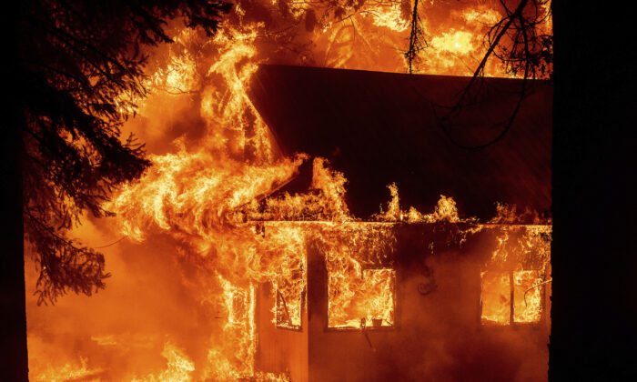 Flames consume a home as the Dixie Fire tears through the Indian Falls community in Plumas County, Calif., on July 24, 2021. (Noah Berger/AP Photo)