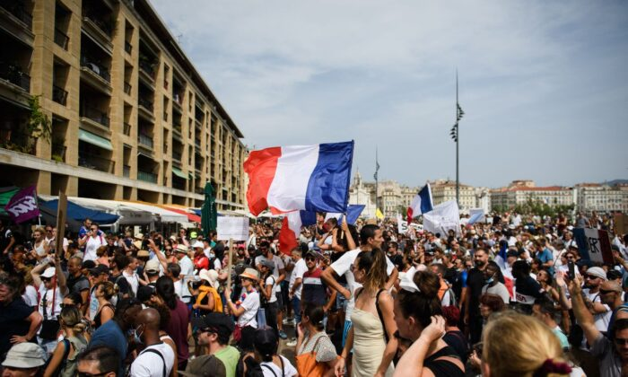 A protestor waves a French national flag during a demonstration against compulsory vaccination for certain workers and the mandatory use of the health pass called by the French government, in Marseille, southern France on July 24, 2021. (Clement Mahoudeau/AFP via Getty Images)