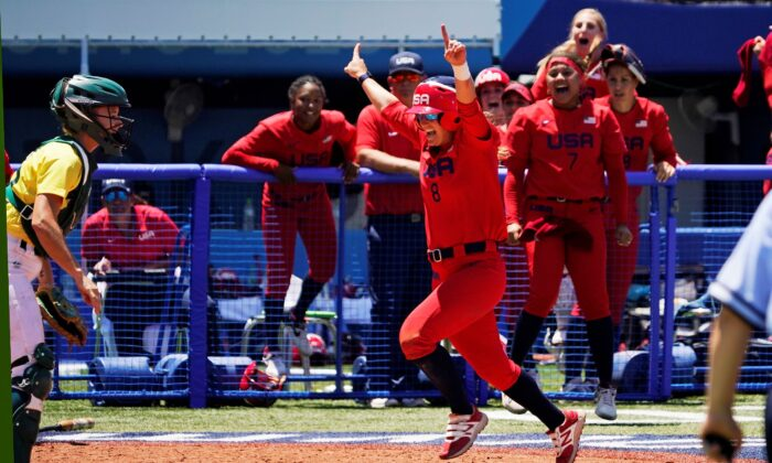 United States' Haylie McCleney scores the game-winning run in front of Australia's Belinda White (L) in the eighth inning of a softball game at the 2020 Summer Olympics, in Yokohama, Japan, on July 25, 2021. (AP Photo/Sue Ogrocki)