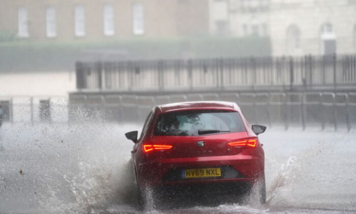 A car drives through flood water in Horse Guards Road in central London on July 25, 2021. (Victoria Jones/PA)