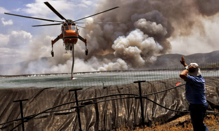 A helicopter is being filled up with water from a tank as a wildfire burns near the village of Spathovouni, near Corinth, Greece, on July 23, 2021. (Vassilis Psomas/Reuters)