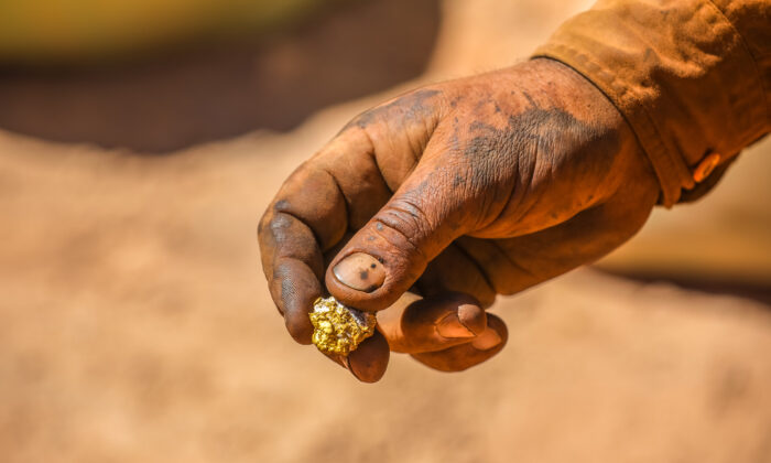 A hand holding a gold nugget. (Emmerson Resources)