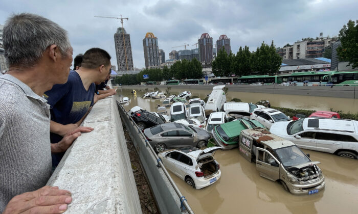 People look out at cars sitting in floodwaters after heavy rains hit the city of Zhengzhou, Henan Province, China, on July 21, 2021. (STR/AFP via Getty Images)
