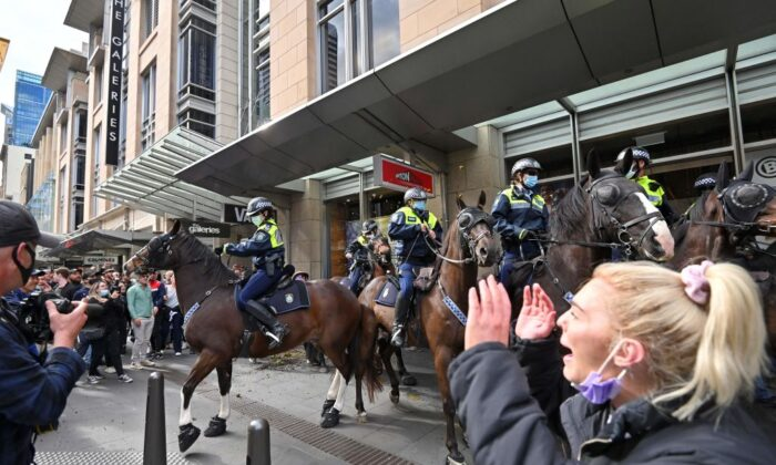 Police officers on horseback disperse protesters during a rally in Sydney, Australiaon July 24, 2021, as thousands of people gathered to demonstrate against the city's month-long stay-at-home orders. (Steven Saphore/AFP via Getty Images)