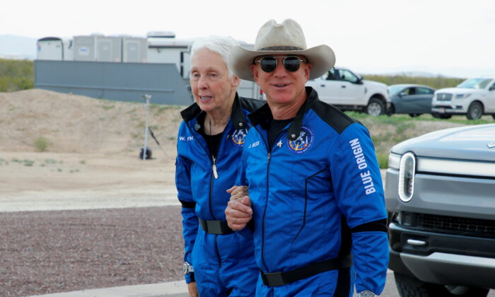 Billionaire American businessman Jeff Bezos walks with crew mate Wally Funk at the landing pad after they flew on Blue Origin's inaugural flight to the edge of space, in the nearby town of Van Horn, Texas, United States, on July 20, 2021. (Joe Skipper/Reuters)