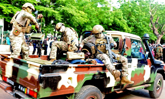 An assailant who attempted to stab Mali's interim president Colonel Assimi Goita during the Eid Al Adha prayer, is seen lying in an army vehicle after he was arrested in Bamako, Mali  July 20, 2021. (Stringer/Reuters)