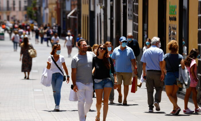 Two tourists walk without face masks in La Laguna on the day the Canary Islands government imposed stricter rules to control a surge in coronavirus disease (COVID-19) cases, on the island of Tenerife, Spain, on July 26, 2021. (Reuters/Borja Suarez)