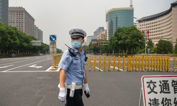 A policeman stands by a barrier to prevent cars to access ChangAn Jie, Beijing's main road leading to Tiananmen Square in Beijing on July 1, 2021. (Andrea Verdelli/Getty Images)