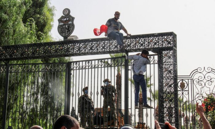 Tunisian soldiers guard the main entrance of the parliament as demonstrators gather outside the the gate in Tunis, Tunisia, on July 26, 2021. (Hedi Azouz/AP Photo)