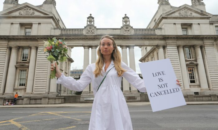 Orla O'Huadaigh holds up a sign at a protest march to Government Buildings in a bid to allow up to 100 guests to attend weddings this year in Dublin, Ireland, on July 27, 2021. (Lorraine O'Sullivan/Reuters)
