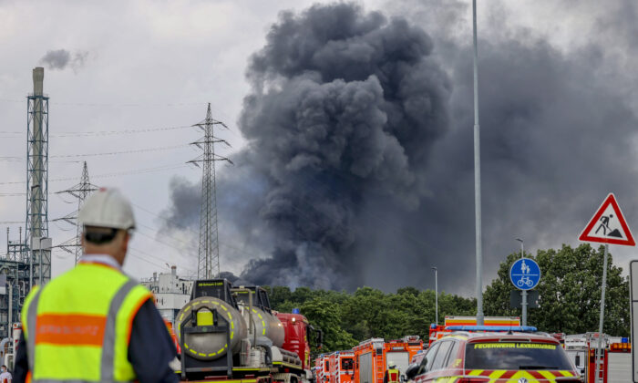 Emergency vehicles of the fire brigade, rescue services, and police stand not far from an access road to the Chempark over which a dark cloud of smoke is rising in Leverkusen, Germany, on July 27, 2021. (Oliver Berg/dpa via AP)