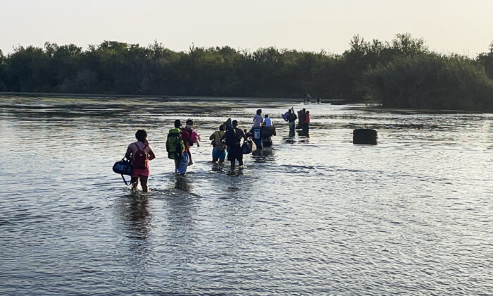 A group of illegal immigrants crosses the Rio Grande from Acuna, Mexico, to Del Rio, Texas, on July 25, 2021. (Charlotte Cuthbertson/The Epoch Times)