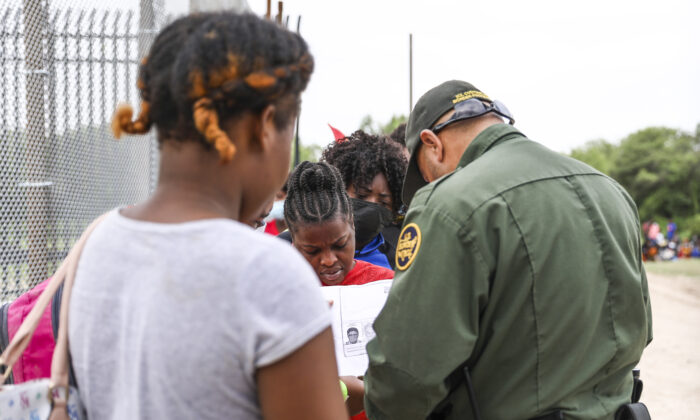 A Border Patrol agent starts organizing a group of more than 350 illegal immigrants after they crossed the Rio Grande from Mexico into Del Rio, Texas, on July 25, 2021. (Charlotte Cuthbertson/The Epoch Times)