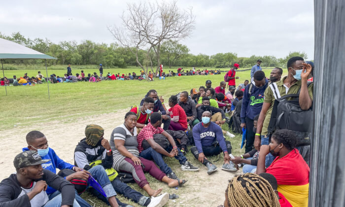 A group of illegal immigrants wait for Border Patrol after crossing the Rio Grande from Mexico into Del Rio, Texas, on July 25, 2021. (Charlotte Cuthbertson/The Epoch Times)