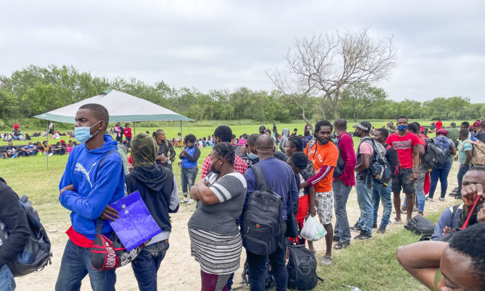 A group of more than 350 illegal immigrants waits for Border Patrol after crossing the Rio Grande from Mexico into Del Rio, Texas, on July 25, 2021. (Charlotte Cuthbertson/The Epoch Times)
