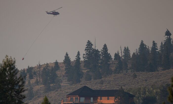 A helicopter carrying a bucket flies over a property in Barnes Lake while battling the Tremont Creek wildfire near Ashcroft, B.C., on July 15, 2021. (The Canadian Press/Darryl Dyck)
