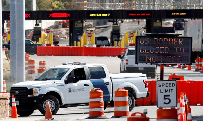 A U.S. Customs and Protection vehicle stands beside a sign reading that the border is closed to non-essential traffic at the Canada-U.S. border crossing at the Thousand Islands Bridge in Lansdowne, Ontario, Canada, on Sept. 28, 2020. (Lars Hagberg/Reuters)