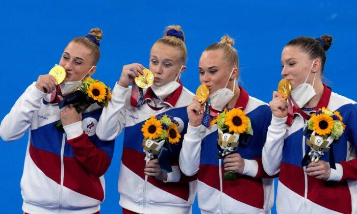 Russian Olympic Committee's artistic gymnastics women's team, from left, Liliia Akhaimova, Viktoriia Listunova, Angelina Melnikova and Vladislava Urazova celebrate after winning the gold medal at the 2020 Summer Olympics, in Tokyo on July 27, 2021. (Gregory Bull/AP Photo)