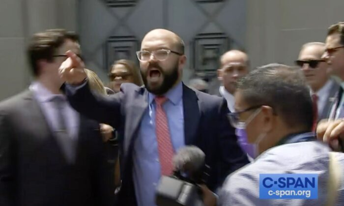 A screenshot from a C-Span video showing the moment Nick Dyer, Rep. Greene's communications director, announces the press conference held by five GOP lawmakers was over, as protesters swarmed the event, outside the Department of Justice in Washington on July 27, 2021. (Screenshot C-Span/The Epoch Times)