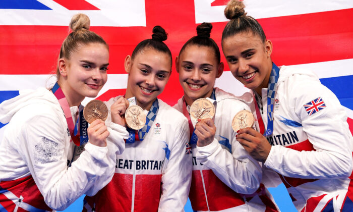 Great Britain's gymnasts Alice Kinsella, Jennifer Gadirova, Jessica Gadirova, and Amelie Morgan celebrate with their bronze medals on the fourth day of Tokyo Olympics 2020. (Martin Rickett/PA)